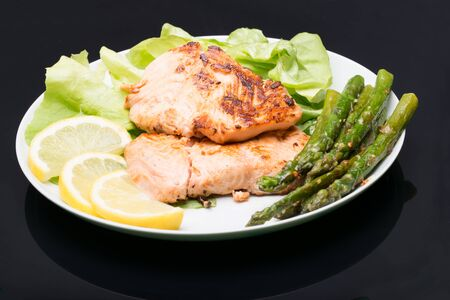 Plate with grilled salmon and cooked asparagus over black background