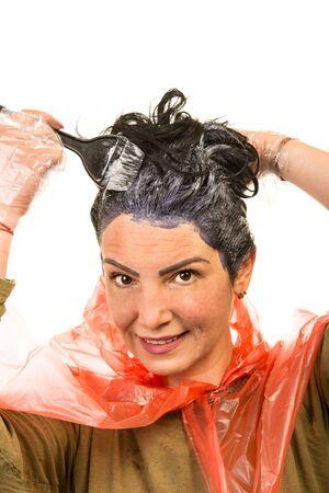 Woman applying dye black hair against white background