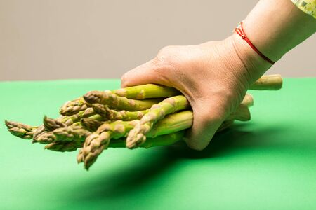 Female hand catching asparagus against green background
