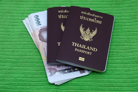 Thailand passport and Thai money isolated on green background photo