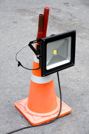 mounted: LED energy saving industrial flood light mounted on orange striped rubber cone