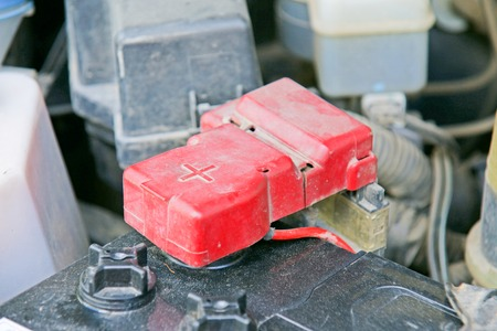 electrolyte: Car battery with red positive polarity for auto concept Selective focus at positive symbol
