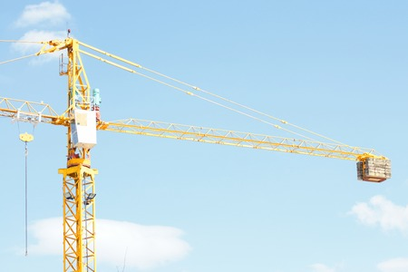 crane: Yellow Industrial crane and blue sky on construction site or seaport