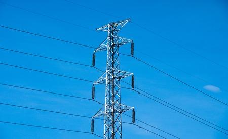 energia electrica: Poste de tensi�n alta o torre de la l�nea de transmisi�n de energ�a y el cielo azul Foto de archivo