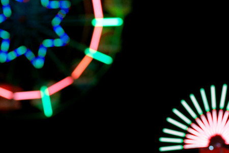 electric avenue: Defocused and blurred image of ferris wheel at amusement park at night for background usage.