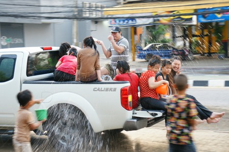 cool down: CHIANGMAI, THAILAND - APRIL 14, 2012 : People in a Songkran water fight festival. Songkran is a joyful summer festival which everybody can splash water to them for cool down from hot weather.
