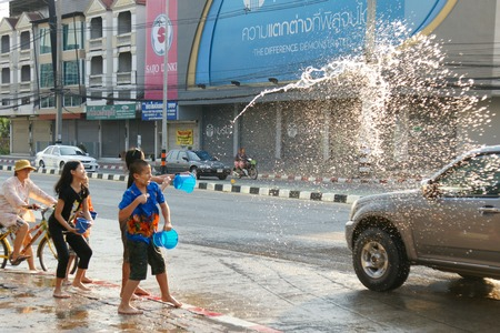cool down: CHIANGMAI, THAILAND - APRIL 15, 2012 : People in a Songkran water fight festival. Songkran is a joyful summer festival which everybody can splash water to them for cool down from hot weather.