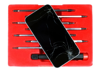 portable failure: Cracked smartphone and screwdrivers set isolated on white background