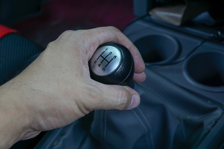 lever: Left hand holding a gear shift lever