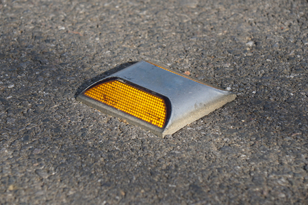 reflective: Metal road stud with yellow reflector on asphalt road in Thailand Stock Photo