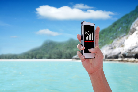No Service showing on the smartphone with tropical island background. Stock Photo