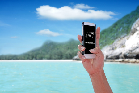 E-mail Sending showing on the smartphone with tropical island background. Stock Photo