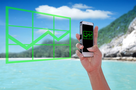 Green rising graph chart showing on the smartphone with tropical island background. Stock Photo