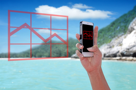 Red falling graph chart showing on the smartphone with tropical island background. Stock Photo