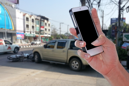 Man using smartphone at roadside after car accident and blurry background  with clipping path on screen panel