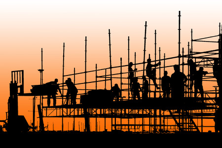 Silhouette of construction workers working on scaffolding