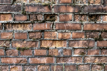 broken brick wall background in sunny summer day. Abstract red brick old wall texture background. Ruins uneven crumbling red brick wall background texture. Фото со стока