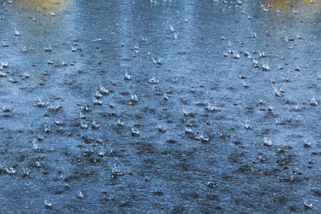 rain raindrops flying and crashing on the asphalt in Sunny weather Stock Photo