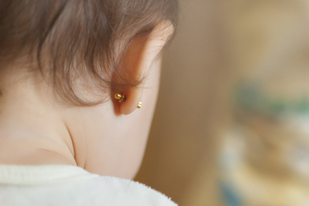 ear piercing for small children, one year old child with pierced ears and dark and curly hair