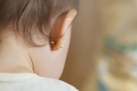 Ohrpiercing für kleine Kinder, einjähriges Kind mit durchbohrten Ohren und dunklen und lockigen Haaren
