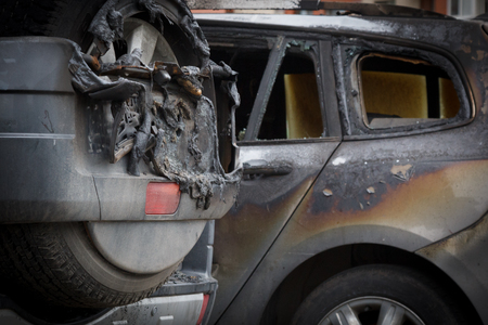 partially burned down family station wagon, side view which have burned doors and completely burned down interior.