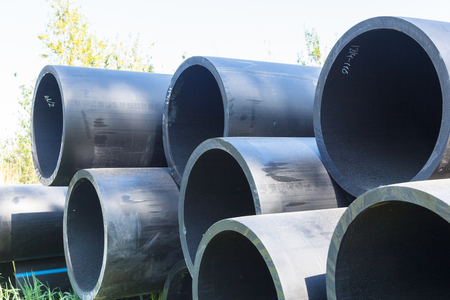 HDPE pipe for water supply at construction site construction of a water supply system plastic pipes for water supply of the city, lie on a grass