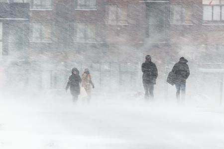 Zamieć, silny wiatr, deszcz ze śniegiem, na tle domów zamazane sylwetki ludzi, starają się ukryć przed złą pogodą, pokonują wszelkie trudności surowego klimatu. idź na przystanek autobusowy.