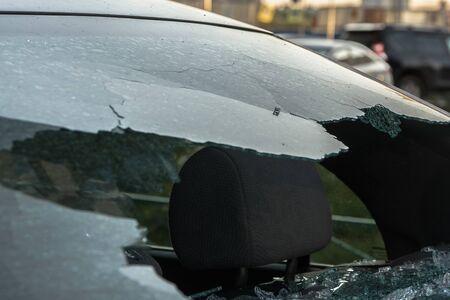 Broken rear glass of car, spread fragments of glass on asphalt.