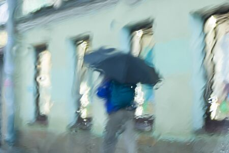 It s raining hard, through the window. Blurred silhouettes of people in the city go about their business 写真素材