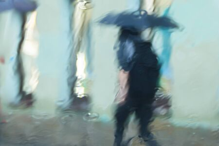 It s raining hard, through the window. Blurred silhouettes of people in the city go about their business Imagens
