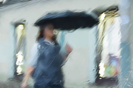It 's raining hard, through the window. Blurred silhouettes of people in the city go about their business Фото со стока