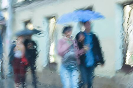 It s raining hard, through the window. Blurred silhouettes of people in the city go about their business Stock fotó