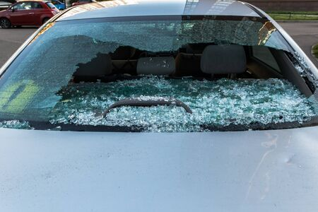 Broken rear glass of car, spread fragments of glass on asphalt