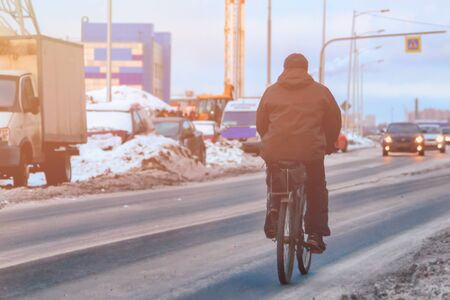 cyclist rides on a slippery road in winter ice