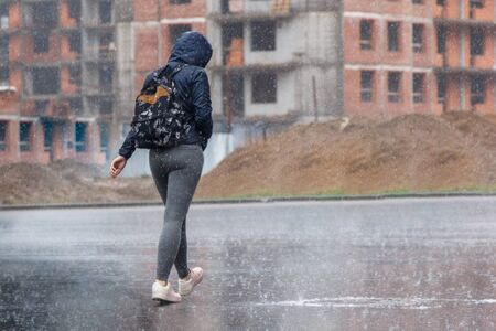 a woman with a backpack and a hood runs in the pouring rain.