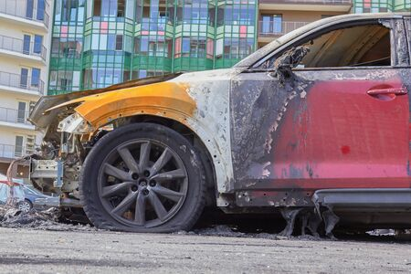 wheels and wheels of a burned-out car in one of the city's districts. Stock Photo