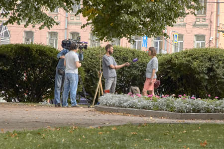 Saint-Petersburg, Russia - 9 August 2019: Professional cameraman and journalist interviews a girl in the city center.
