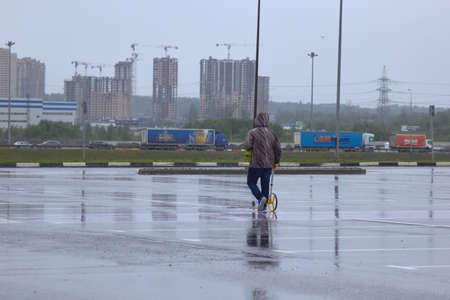 Russia, Saint-Petersburg, 10 August 2019: A worker walks with a measuring wheel measuring the road in the rain