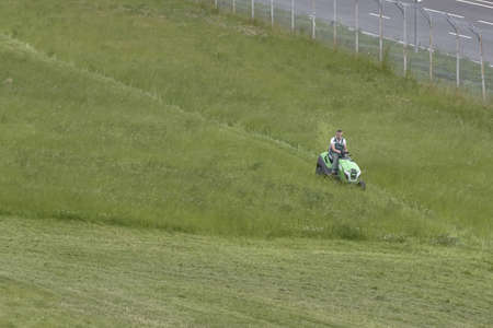 Russia, Saint-Petersburg, July 2019: lawnmower tractor works on a large area with lawn. Редакционное