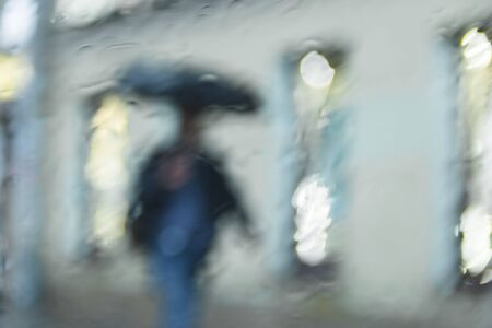 It 's raining hard, through the window. Blurred silhouettes of people in the city go about their business selevtive focus