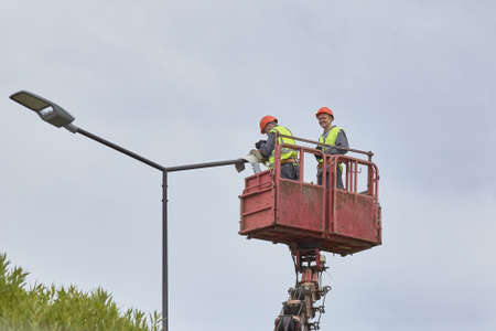 Saint Petersburg, RUSSIA - July 11, 2019: workers in lift bucket repair street light pole with double head and change the lighting to diode.