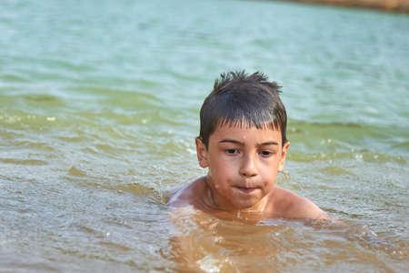 cute boy bathing in water in a lake in nature. Foto de archivo