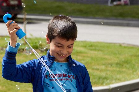 boy blowing bubbles in the summer sun joy. 免版税图像