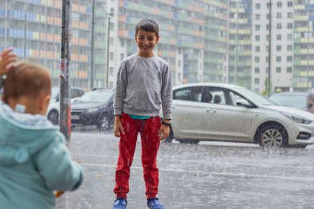 a child in the rain rejoices in a sudden heavy rain, city children. 免版税图像