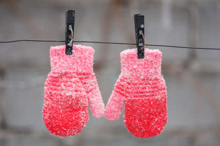 Red mittens hanging on a clothesline in winter in the cold Foto de archivo