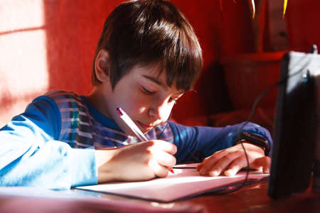 home online training, a boy using a mobile phone and headphones is engaged in English speaking with a teacher on an online conference call 免版税图像