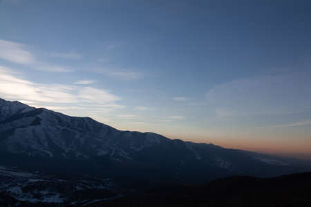 Beautiful landscape in the mountains at sunset. View of the misty hills hidden behind the oncoming darkness 免版税图像