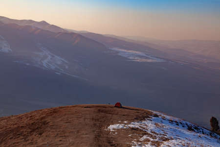A lone tent high in the mountains against the backdrop of the greatest mountain slopes. Evening by the campfire in the mountains. Camping in tents in the mountains. 免版税图像