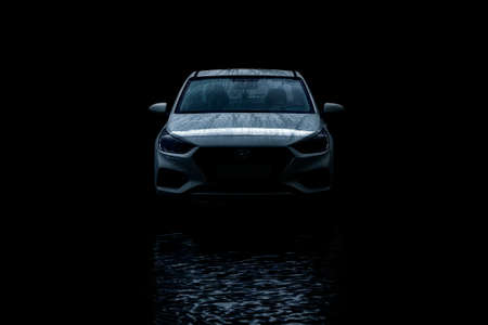 Saint Petersburg, Russia june 2019: Car with raindrops on the hood on a black background in the reflection of water Hyundai Solaris 2018