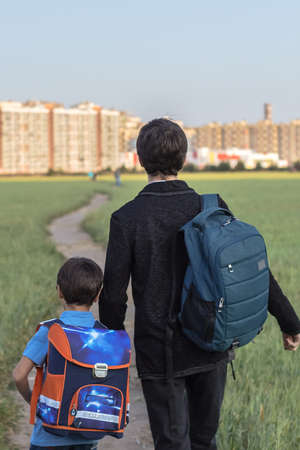 Teen, 12, and his younger brother, 6, hold hands amid urban landscape and huge pitch